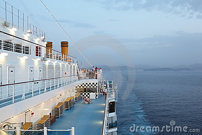 Big cruise ship riding in evening. light on.