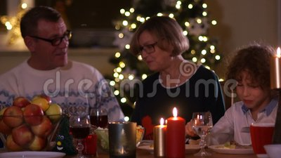Big family with children celebrating Christmas at home. Festive dinner at fireplace and Xmas tree. Parent and kids. Eating at fire place in decorated room stock footage