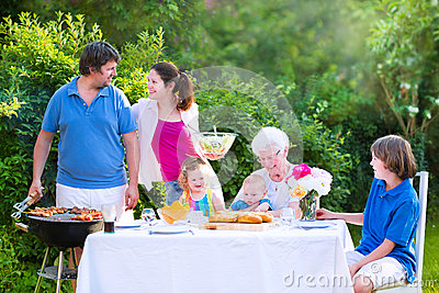 Big family grilling meat for lunch with grandmother