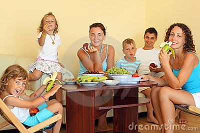 Big happy family eats fruit in cosy room