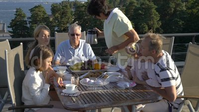A big happy family has dinner on the open terrace on the roof of the house. Tea party on the summer terrace on the sea coast stock video