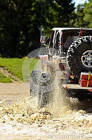 Big Jeep splashing mud in the mountains