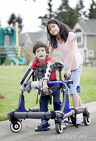 Big sister helping disabled brother walk