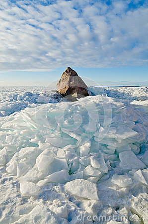 Big stone in the ice on the Baltic Sea
