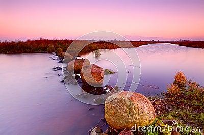 Big stones on river at sunrise