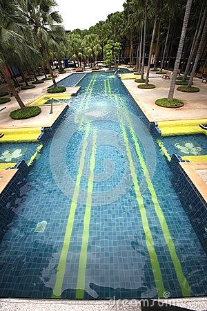 A big swimming pool with clear water and seats in water in the Nong Nooch tropical botanic garden near Pattaya city in Thailand