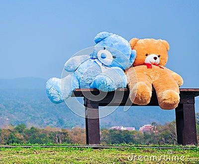 Big teddy bears sitting on wood chair