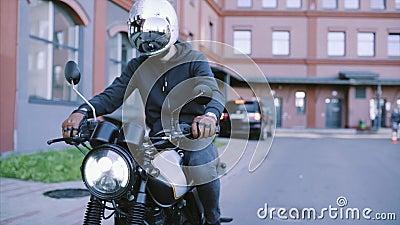 Biker em luvas de couro e capuz preta inicia moto video estoque