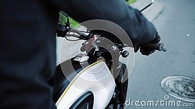 Biker em luvas de couro e capuz preta inicia moto filme