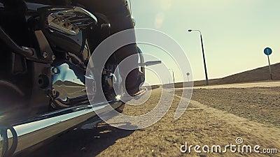 Biker em uma moto, andando em uma pista reta com asfalto ruim, dia ensolarado filme