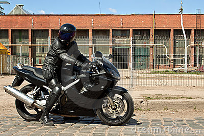 Biker riding motorcycle in old factory