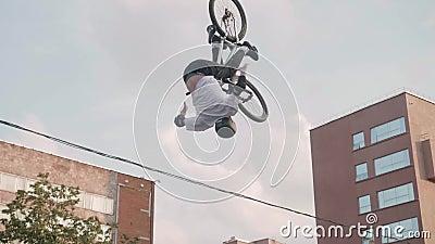 Biker salta e vira-se O edifício da cidade e o céu estão no fundo filme