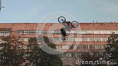 Biker salta e vira-se O edifício da cidade e o céu estão no fundo vídeos de arquivo