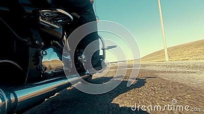 Biker sobre um motochopper dirigindo na estrada, através do deserto, em direção à ponte Vista da retaguarda da perna dos motocicl filme