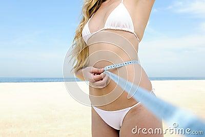Bikini body: Woman measuring her waist