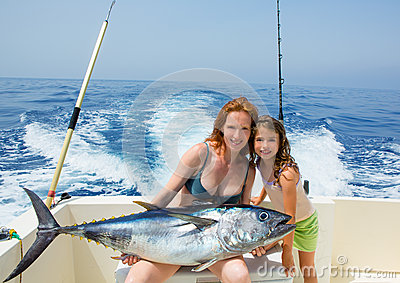 Bikini fisher woman and daughter with bluefin tuna
