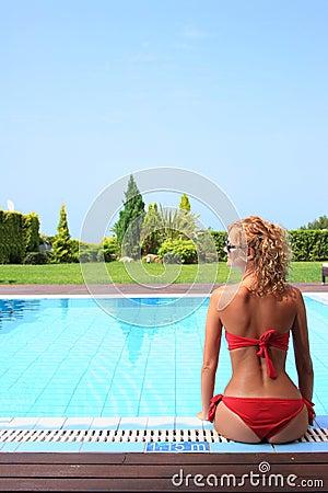 Bikini model in pool with clear blue water