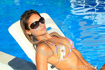Bikini model in pool with clear blue water