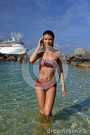 Bikini model standing at shallow water