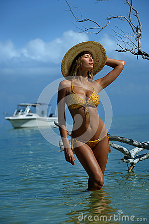 Bikini model in straw hat posing sexy in front of camera at tropical beach location