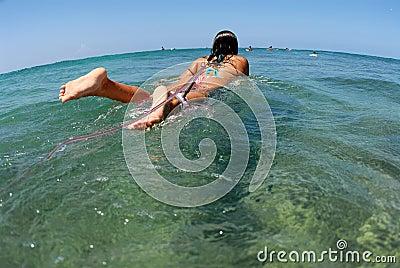 Bikini surfer girl paddling ou