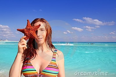 Bikini tourist woman holding starfish