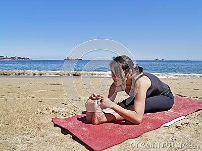 bikram yoga paschimottanasana pose at beach royalty free