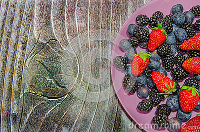 Bilberries and strawberries on a pink plate