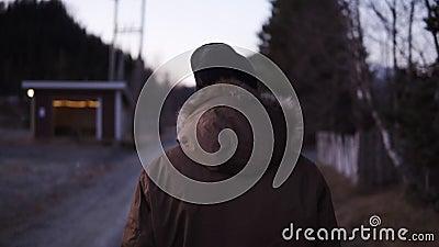 Bild från baksidan av en man som går längs landskapsvägen på kall hösteftermiddag Svart hatt och vinter arkivfilmer