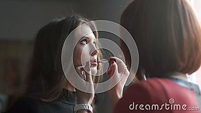 Bilden Sie den Künstler, der Make-up für Modell tut Lipglossanwendung stock video footage