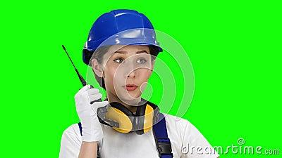 Bildermeisje die dragend besprekingen op de walkie-talkie dragen Het groene scherm Sluit omhoog stock videobeelden