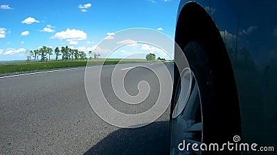 Bilen börjar att flytta sig från en vägren av en huvudväg i bygd i en solig sommardag Kameran monteras på en sida av bilen stock video