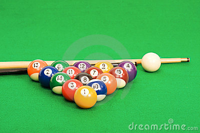 Billiard balls arranged on a green pool table