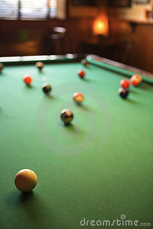 Billiards table with pool balls spread out.