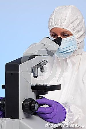 Biochemist looking through a microscope