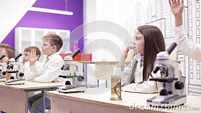 Biologie d'école primaire, classe de chimie - enfants regardant par le microscope banque de vidéos