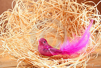 Bird in straw nest with pink feathers and glitter