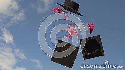Birretes que vuelan en el cielo azul, tradición de la universidad para lanzar los casquillos académicos para arriba metrajes