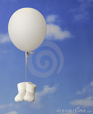 Birth concept:balloon with white baby booties