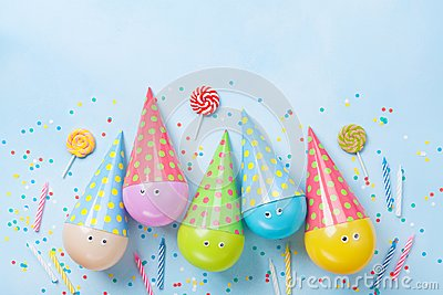 Birthday or party background. Funny balloons, candy and confetti on blue table top view. Flat lay. Invitation card. Stock Photo