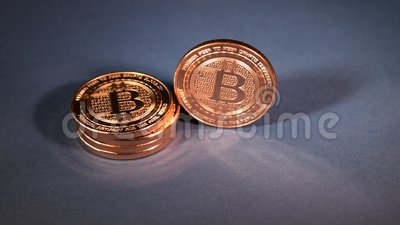 Bitcoin Copper Rounds Standing, Finance Illustration. Stack of bitcoin copper rounds, one of them standing and toppling down on dark blue studio background for stock video