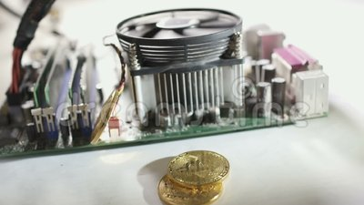 Bitcoins valt onderaan dichtbij werkende motherboard in slowmotion stock videobeelden
