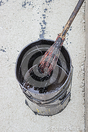Bitumen Emulsion in metal bucket which is applied with a broom