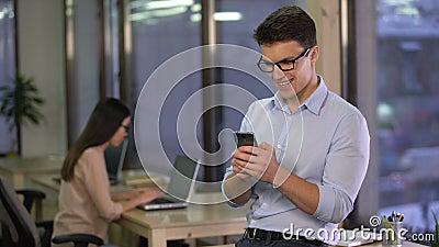 Biurowego pracownika gawędzenie w ogólnospołecznym medialnym gonu na smartphone, komunikacja zdjęcie wideo