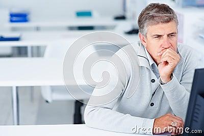 Biznesowego komputeru mężczyzna przyglądający ekran