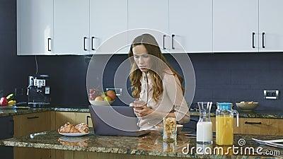 Biznesowej kobiety dopatrywania wideo na komputerze Skoncentrowana kobieta pije kawę zbiory