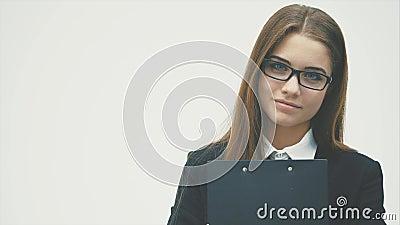 Biznesowi dama stojaki na białym tle Ja trzyma czarną falcówkę z dokumentami i patrzeje blisko przy kamerą zdjęcie wideo