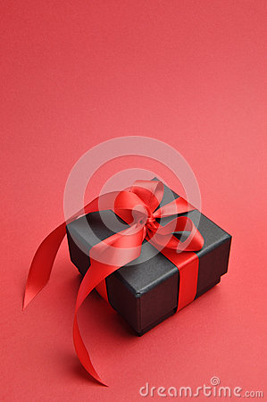 Black box romantic gift with red ribbon, vertical with copy space.