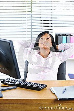 Black businesswoman resting at desk