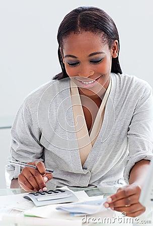 Black businesswoman using a calculator